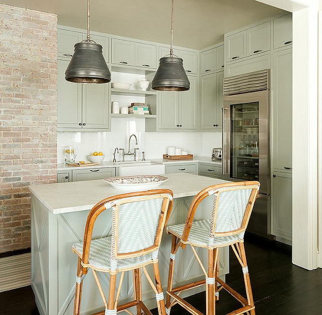 Small Kitchen. Small kitchen features a pair of metal pendants illuminating a gray green center island lined with green French bistro counter stools. Kitchen with gray green cabinets paired with honed white marble countertops and a white quartz tiled backsplash. Kitchen boasts stacked shelving over a small farmhouse sink and a deck mount faucet next to a glass front refrigerator. Jenny Wolf Interiors.