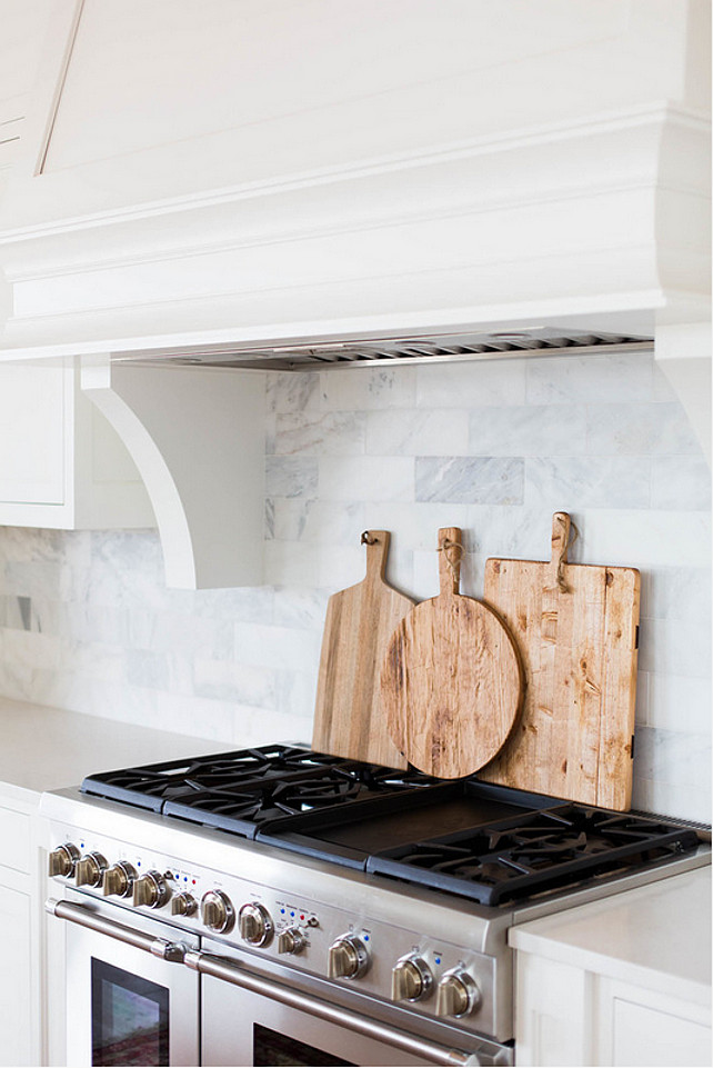 White Marble Brick Backsplash. A white kitchen hood with corbels stands over a white and grey marble brick tiled backsplash and a stainless steel stove lined with cutting boards. #MarbleBacksplash #KitchenBacksplash #Backsplash #KitchenMarbleBacksplash Ashley Winn Design.