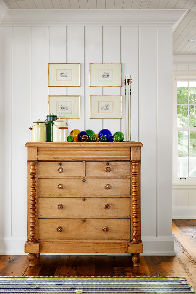 Unpainted Furniture Ideas. Some furniture is best left unpainted! This untouched pine spindle dresser adds handsome wood tones just off the dining room, while a palette of yellow, green, and indigo keeps the display of outdoor-themed finds—glass floats, camp pails, and antique arrows set in wax—feeling curated, not cluttered. #UnpaintedFurniture #FurnitureIdeas Designed by Sarah Richardson.