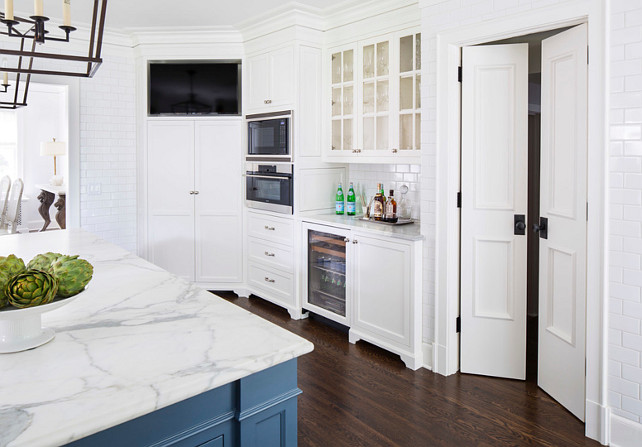 Kitchen Butler's Pantry and Bar Cabinet. Kitchen with butlers pantry and bar cabinet, floor-to-ceiling wall tile, pantry door, built-in ovens and built-in TV. The kitchen Countertop is Calcutta Gold Extra Marble. #Kitchen Martha O'Hara Interiors.