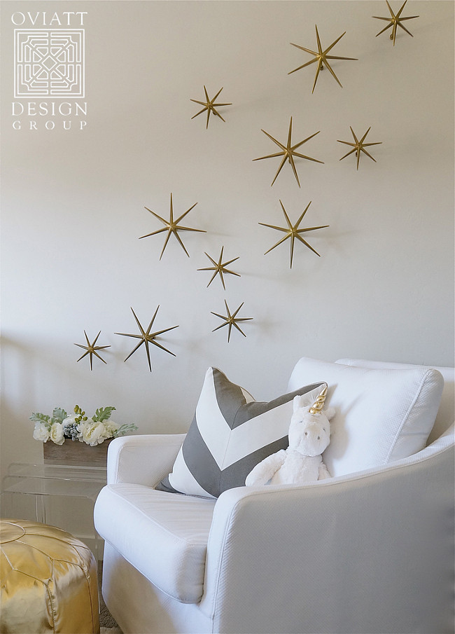 Neutral Gender Nursery. White and gold nursery boasts a white slipcovered glider lined with a gray chevron pillow next to a gold Moroccan pouf placed under gold wall stars, Global Views Etoile Brass Wall Décor. #Neutral #Genger #Nursery Oviatt Design Group.