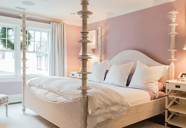 Lavender Bedroom. White and lavender bedroom features lavender walls framing a carved wood 4 poster bed dressed in white and lavender bedding flanked by white campaign nightstands with shelves accented with x trim atop gray geometric rug. #Lavender #Bedroom Brookes and Hill Custom Builders.