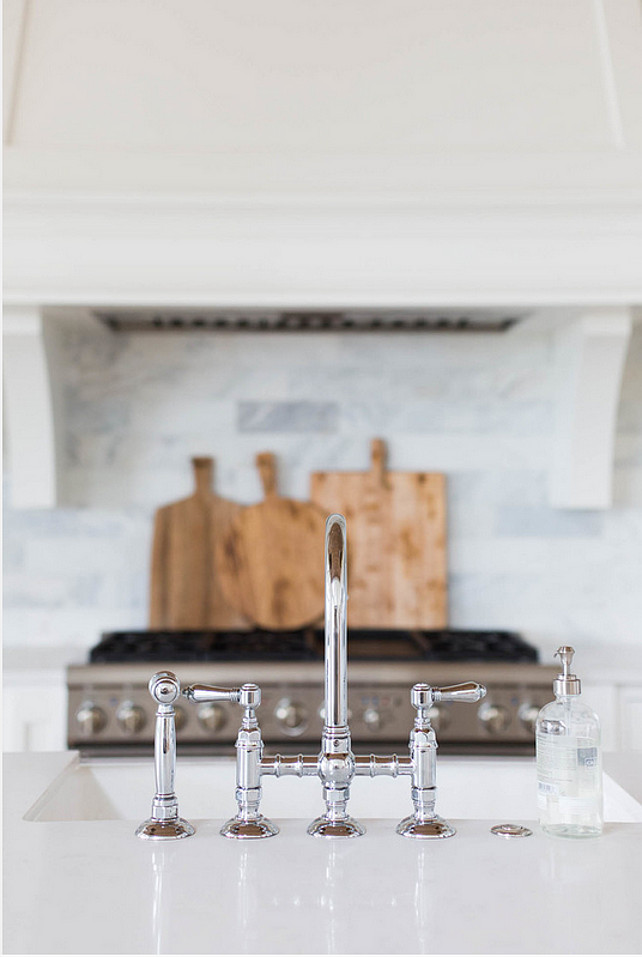 Kitchen Faucet. Kitchen island topped with white quartz fitted with a farmhouse sink and deck mount faucet. A white kitchen hood with corbels stands over a marble brick tiled backsplash and a stainless steel stove. The kitchen faucet is the Rohl Polished Nickel Country Kitchen Three Leg Bridge Faucet. #KitchenIsland #KitchenFaucet #Faucet #Kitchen Ashley Winn Design