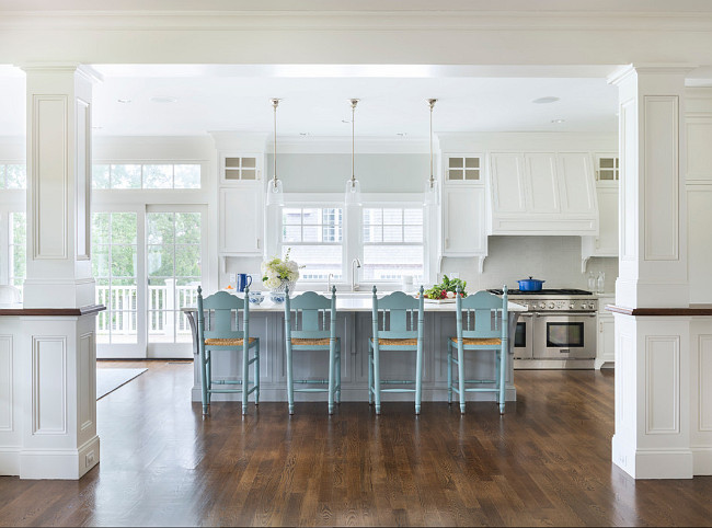 Turquoise Blue Kitchen Counter Stools. White and blue kitchen features three glass pendants illuminating a grey center island topped with white marble lined with turquoise blue counters tools with rush seats. #TurquoiseBlue #Kitchen #CounterStools Digs Design Company.