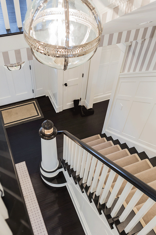 Foyer. Staircase Runner. Foyer features upper walls clad in white and gray stripe wallpaper and lower walls clad in board and batten which extends to the staircase with lighthouse banister light lined with a bound sisal rug illuminated by a Restoration Hardware Victoria Hotel Pendant. #Foyer #Staircase #StaircaseRunner Brookes and Hill Custom Builders