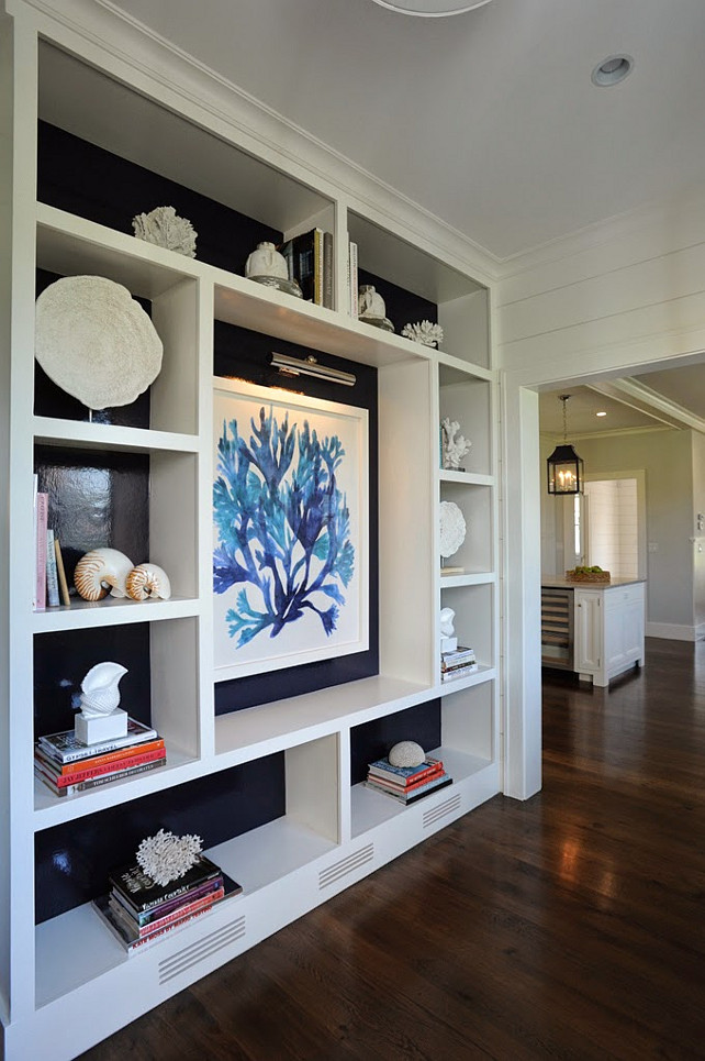 Built-in cabinet. Living Room Built-in Display Cabinet. Living Room with custom Built-in Display Cabinet. The living room features a custom built-in display cabinet just before entering the kitchen area. Notice the large seaweed art print against the dark glossy navy blue backdrop, lit by a library wall sconce. The shelves display stacked books, coral and seashells. #LivingRoom #Cabinet #Builtin #DisplayCabinet #Bookshelves #Bookcase Nina Liddle Design.