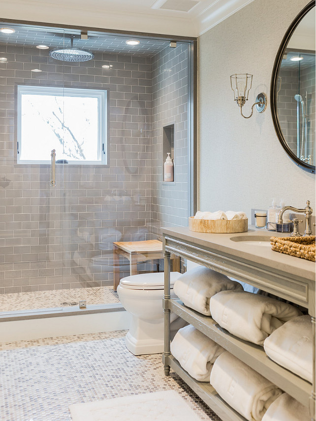 Bathroom. Gray Bathroom. Gray Bathroom Vanity. Gray bathroom features gray walls framing a round rivet mirror illuminated by uplight cage sconce over a gray French bath vanity with shelves filled with fluffy white towels topped with gray countertop framing a round sink paired with a hook and spout faucet beside toilet atop white and gray penny tiled floor. A master bathroom shower boasts gray subway tile surround framing window and tiled niche alongside a ceiling mounted rain shower head over white and gray penny tiled shower floor finished with a seamless glass shower door. #Bathroom #GrayBathroom Brookes and Hill Custom Builders.