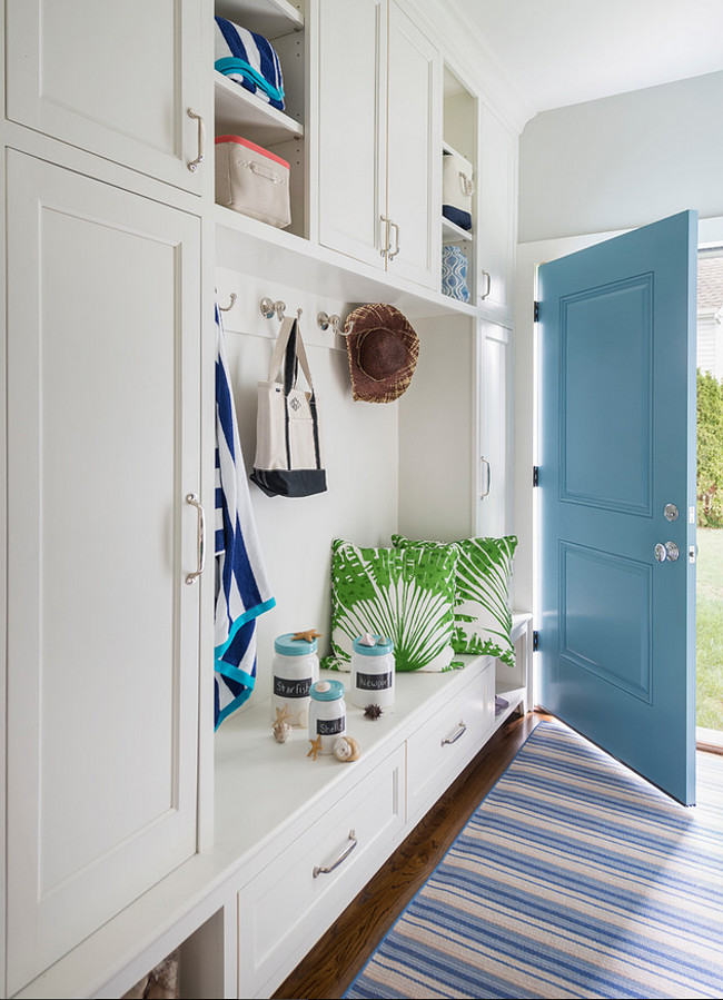Mudroom. Turquoise door in mudroom. The mudroom features a wall of floor-to-ceiling built-in mudroom cabinets. The cabinets features a mudroom bench with drawers under overhead shelves. This space also boasts a white and blue stripe runner placed in front of a turquoise door. Isn't it this a perfect mudroom? #Mudroom #Turquoise #Door #PaintColor Digs Design Company.