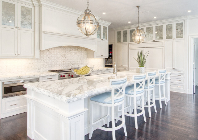 Classic White Kitchen. Classic white kitchen with antique mirror cabinets. Exquisite kitchen features a pair of Restoration Hardware Victoria Hotel Pendants illuminating an super long center island topped with white marble framing square sink and polished nickel faucet lined with white and blue counter stools. A curved kitchen hood stands over a mosaic marble backsplash and a Wolf Range with an under the counter microwave to the left. The back wall of the kitchen is fitted with antiqued mirrored cabinets stacked over pantry cabinets flanking a paneled refrigerator and freezer. Anne Hepfer Designs.