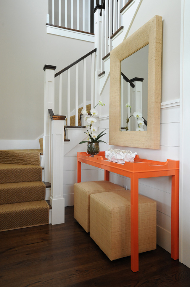 Foyer. Coastal Foyer. Coastal Entrance Foyer. With a hint of color, this stunning foyer features shiplap walls, a wraparound staircase with a sisal stair runner beside an Oomph Fenwick Console Table, with a pair of raffia wrapped poufs and a rectangular raffia mirror. #Foyer #Entryway #Entrance Nina Liddle Design.