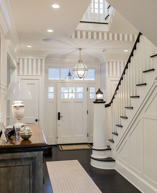 Foyer. Entry foyer. Entry foyer door. Entry foyer door and sidelights. Entry foyer paneling wall. Entry foyer ebony flooring. Entry foyer white walls. Entry foyer lighting. Entry foyer staircase. Entry foyer board and batten. Entry foyer stripe wallpaper. Entry foyer gray stripes. #Entry #foyer Brookes and Hill Custom Builders.