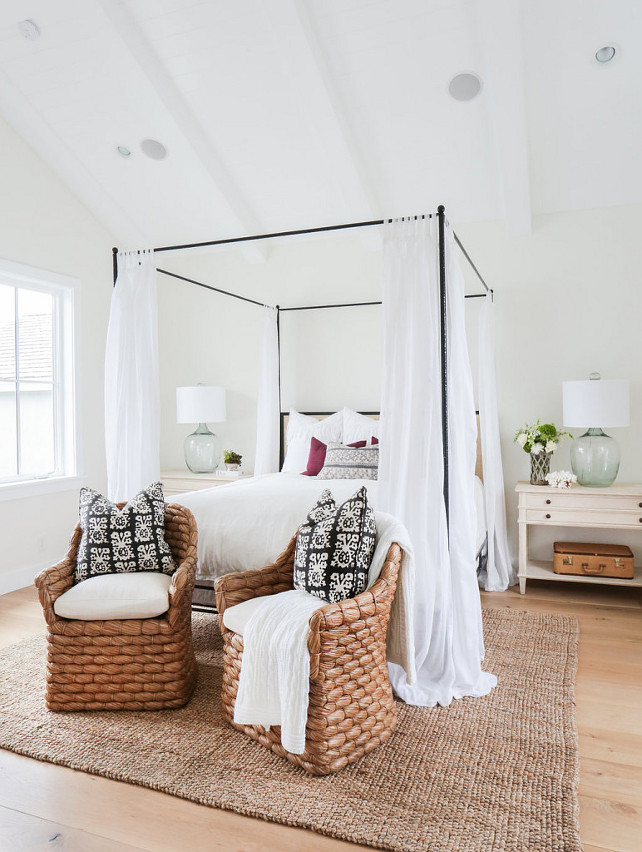 This beach-y bedroom features a vaulted ceiling with white wood beams over an iron canopy bed. The whitewashed wood farmhouse nightstands are decorated with recycled glass lamps and fresh flowers. Notice the wide plank floors, the seagrass chairs with black and white pillows and the jute rug.
