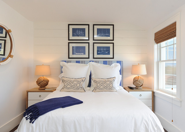 Blue and White bedroom. Coastal Blue and White bedroom. Beach house Blue and White bedroom. Nautical Blue and White bedroom. Nautical bedroom with shiplap clad accent wall featuring framed sailboat blueprints over a blue striped headboard on bed layered with white bed linens topped with blue sailor knot pillows and a blue fringed rug throw. A pair of two-tone nightstands stand on either side of the bed topped with Pottery Barn Rope Knot Table Lamps with a Serena and Lily Montara Mirror.