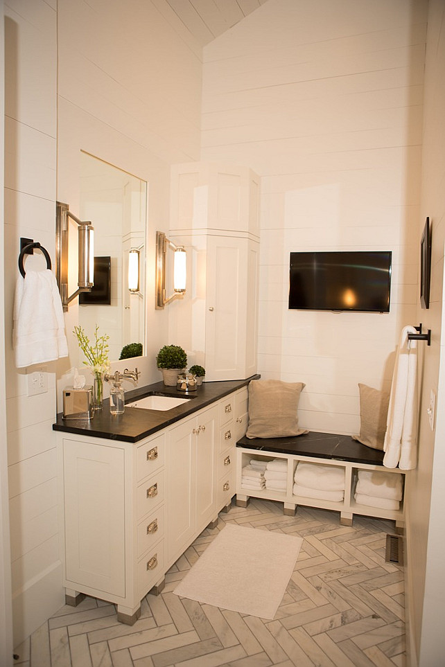 Master Bathroom Ideas. Master bathroom features a white washstand topped with soapstone under an inset mirror illuminated by Eclipse Wall Lights next to a corner cabinet and a built-in soapstone bench with open cubbies filled with fluffy white towels situated under a flatscreen TV alongside a marble herringbone floor. #MasterBathroom #Bathroom Hahn Builders.