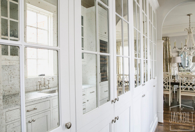 Antique Mirror Kitchen Cabinet. Kitchen boasts a wall of white pantry cabinets adorned with nickel knobs fitted with antiqued mirrored cabinet doors. #AntiqueMirror #Kitchen #Cabinet JackBilt Homes.