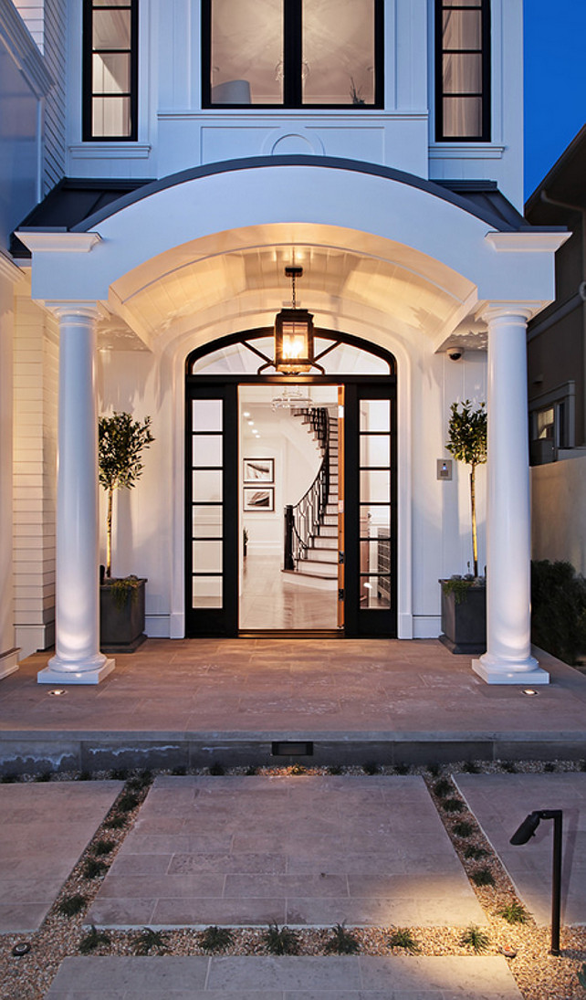 Arched Front Door. Arched portico. White house with Black trim. Entrance. Front door. Lantern. White house Spinnaker Development.