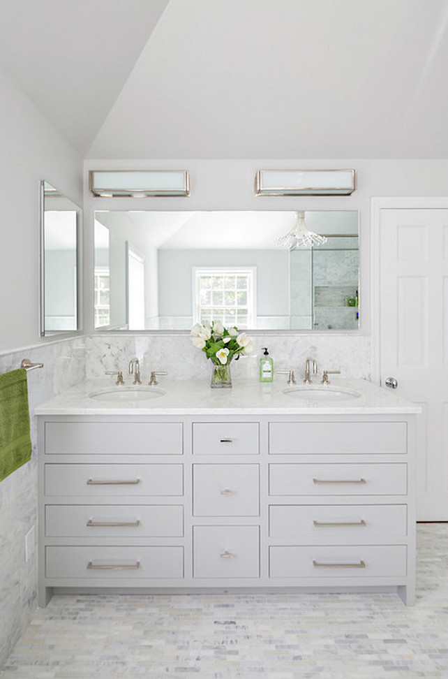 Bathroom Cabinet Ideas. White and gray bathroom features upper walls painted gray and lower walls clad in marble wainscoting finished with marble pencil tiles framing a light gray dual bathroom vanity topped with white marble framing round sinks under frameless full length vanity mirror lit by two long box sconces atop linear marble tiled floor adjacent to wall lined with inset frameless medicine cabinet. #bathroom Clean Design Partners