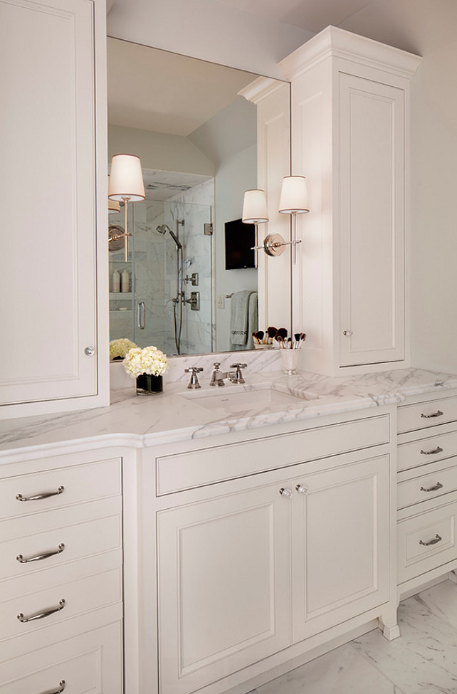 Bathroom Cabinet Ideas. Bathroom features his and her vanities with custom cabinetry, Calacatta marble, quality fixtures, and ample storage. White Bathroom Cabinet Design. #BathroomCabinet #BathroomCabinetry Bartelt.