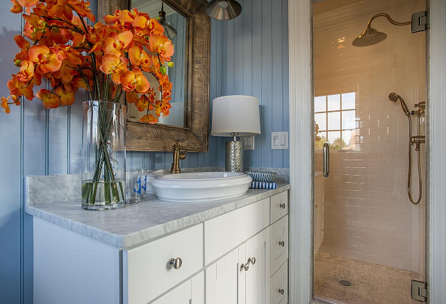 Bathroom Shower Ideas. Crisp white hues displayed in the vanity cabinetry and above the sink transition through the glass shower door into classic subway tiles.
