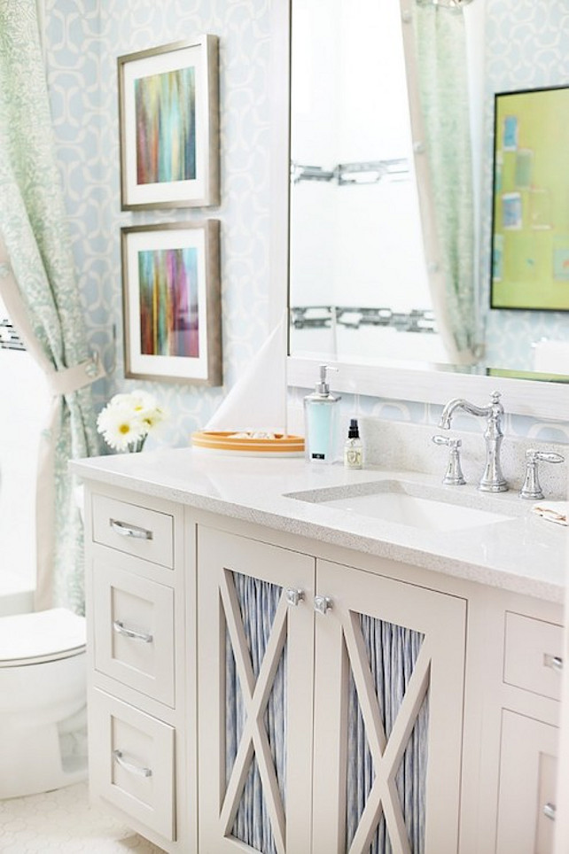Bathroom. Pretty bathroom features white and blue geometric wallpaper on walls which highlight a pair of framed abstracts hung over the toilet to the left of an ivory sink vanity with x-front cut out cabinet doors dressed in blue fabric below an ivory Corian countertop which frames an undermount porcelain sink and hook spout faucet below a matching ivory mirror. #bathroom  UV Parade of Homes