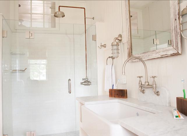Bathroom. Coastal Bathroom Design Ideas. The vanity was custom made and the sink used was a porcelain farmhouse sink. The lights are from Urban Archaeology. #Bathroom #CoastalInteriors