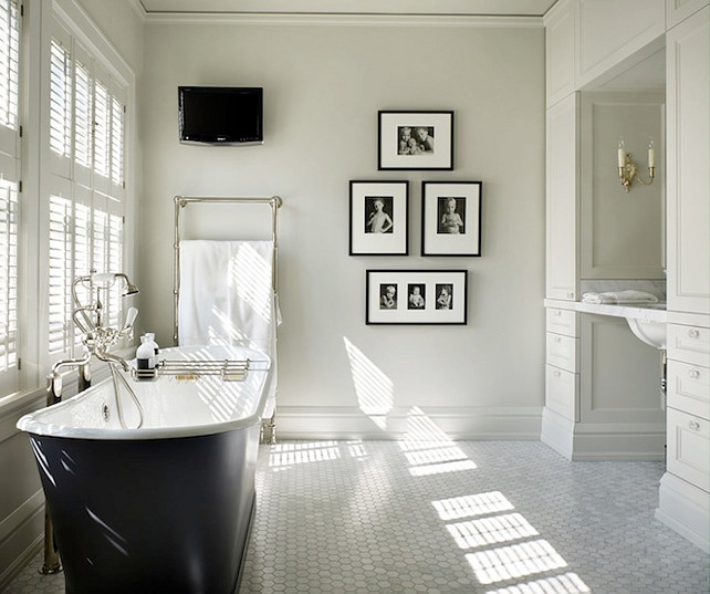 Bathroom. Blacj and White Bathroom. Black and white bathroom with cast iron tub with floor-mount tub filler and bath caddy placed in front of windows covered in plantation shutters over carrara marble hex tile floor. Bathroom features floor to ceiling white built-in cabinets and carrara marble top floating vanity. Bathroom wall with TV, wall-mounted towel warmer and collection of black and white family photos in black gallery frames. Master Bathroom. Toth Construction.