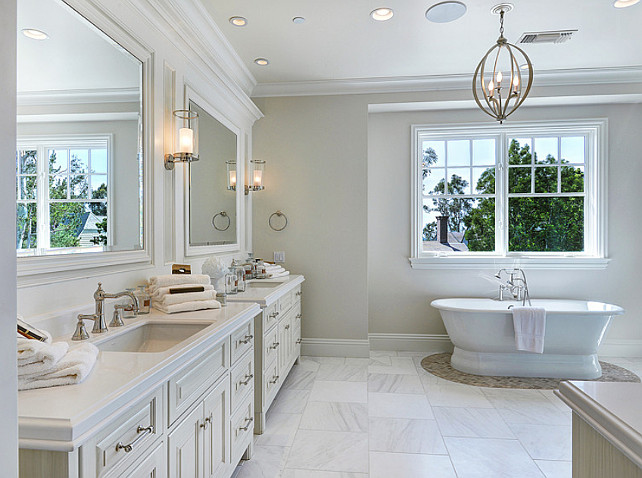 Bathroom. Neutral Bathroom Ideas. The master bathroom features custom his and hers vanity painted in an ivory color. The freestanding bath is framed by pebble flooring. #NeutralBathroom