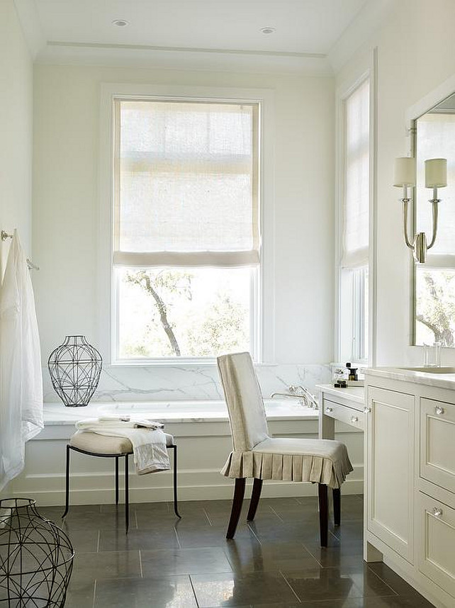 Bathroom. Transitional bathroom features an ivory wainscoted tub with a marble deck and backsplash placed under windows dressed in a natural linen roller shades. Interior Design by Beth Webb Interiors.