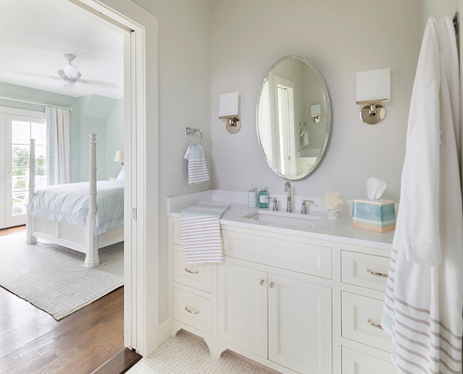 Bathroom. White and soft gray bathroom. Bathroom with off-white cabinet, white countertop and soft gray walls. This color scheme looks great with the flooring. #barhroom Digs Design Company.