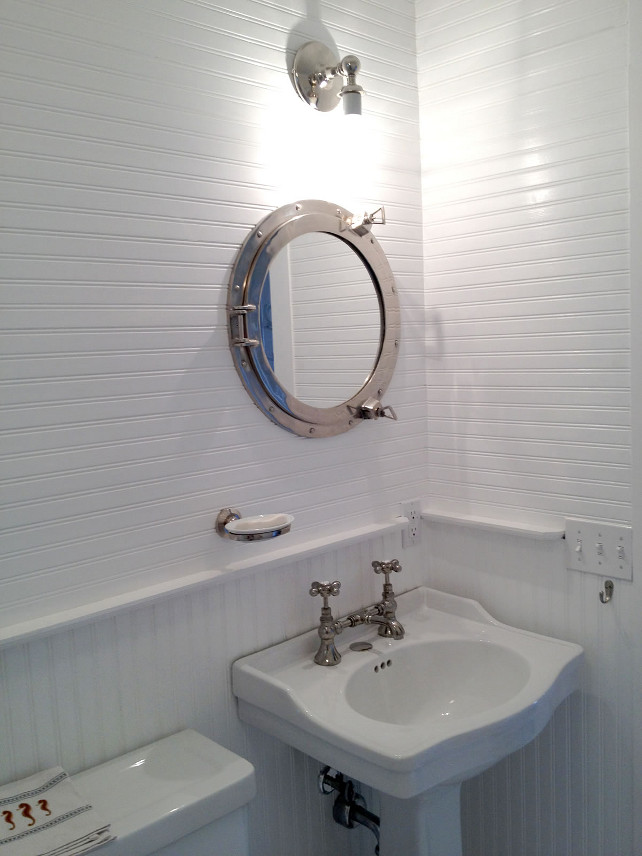 Beadboard Bathroom. White Beadboard Bathroom. Coastal Bathroom with White Beadboard Walls. The powder room features custom white beadboard walls and a coastal mirror. This porthole was sourced from a shipyard graveyard, refinished and converted into a medicine cabinet. Fits perfectly with the theme of the house.  #Beadboard #Bathroom #WhiteBeadboard #BeadboardWall