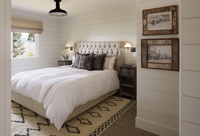 Bedroom with shiplap paneled walls over gray washed hardwood floors layered with a Moroccan style wool rug. Designed by Artistic Designs for Living.