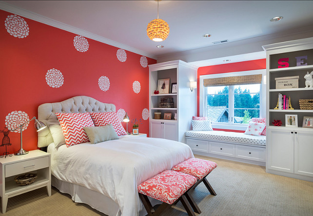 Bedroom. Kids Bedroom Ideas. Kids Bedroom with stencilled walls. Girls bedroom features painted coral walls, custom tufted headboard, custom x benches, nightstands, custom painted bookshelves, window seat with bench, woven roman shades, Etsy Dahlia wall decals. #Bedroom #KidsBedroom