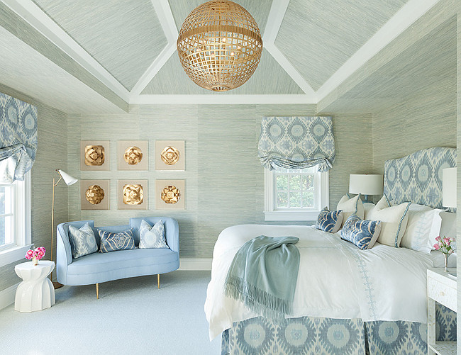 Blue and gray bedroom features walls and ceiling clad in gray grasscloth wallpaper lined with a blue ikat headboard and brass cage globe lantern. Anna Burke Interiors.