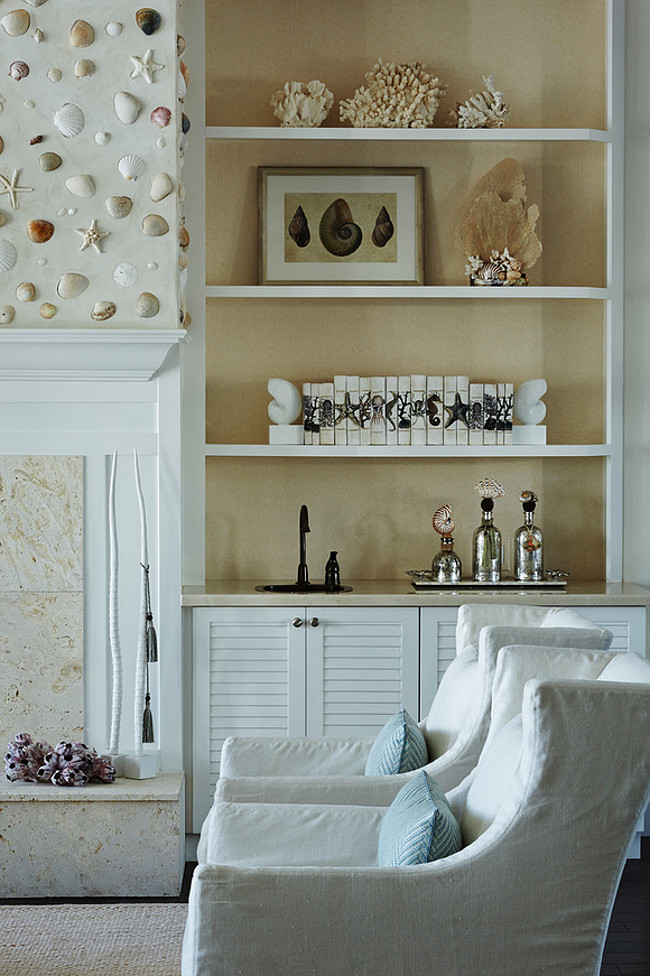 Bookcase Decor. Coastal living room bookcase decor. Coastal living room with shell fireplace and built-in bookcases on both sides. #Coastal #LivingRoom #bookcase JMA Interior Design.