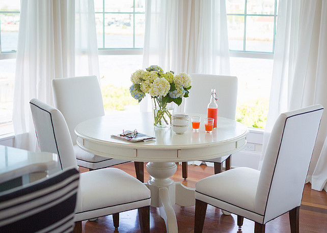 Breakfast Nook. Beautiful breakfast nook fills bay window dressed in white cotton drapes with a Cornice Hanging Lantern mounted over a white pedestal dining table lined with white dining chairs with black piping. #BreakfastNook
