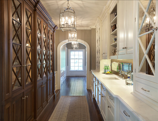 "Butler's Pantry with plenty of cabinets and Calacatta marble counters. This is an extraordinary butler's pantry design, with Calacatta marble countertop, white glass-front cabinets and lantern pendant lighting. Lantern Pendants are the ""Visual Comfort CHC3421BZ Chart House 4 Light Small Arch Top Lantern"". #ButlersPantry #Pantry #CabinetDesign Designed by Yunker Associates Architecture."