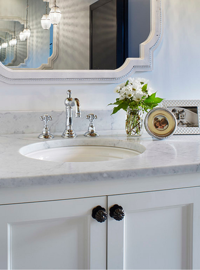 White bathroom vanity with Carrara marble countertop and the bathroom faucet is by Rohl. The bathroom cabinet is painted in BM White Dove. Martha O'Hara Interiors.