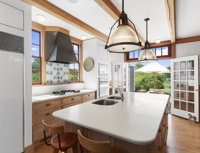 Charming Cottage Kitchen. Cottage Kitchen with traditional blue and white backsplash, aged white oak cabinets, exposed ceiling beams and industrial pendant lighting above island. #Kitchen #Cottage #CottageKitchen .
