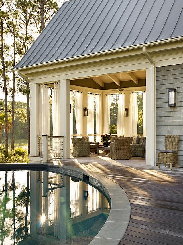 Circular Pool. Cottage home features a circular in-ground pool next to a covered deck filled with wicker furniture finished with white grommet outdoor drapes. Interior Design by Beth Webb Interiors.