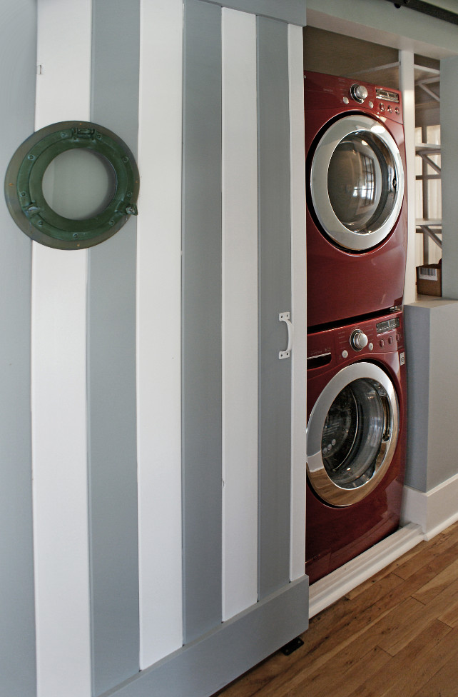 Closet Laundry Room. Closet Laundry room. This closet laundry room is located in the hallway and features a striped barn door painted in white and gray . A marine window adds coastal charm to this laundry room.  #LaundryRoom #ClosetLaundryRoom #BarnDoor