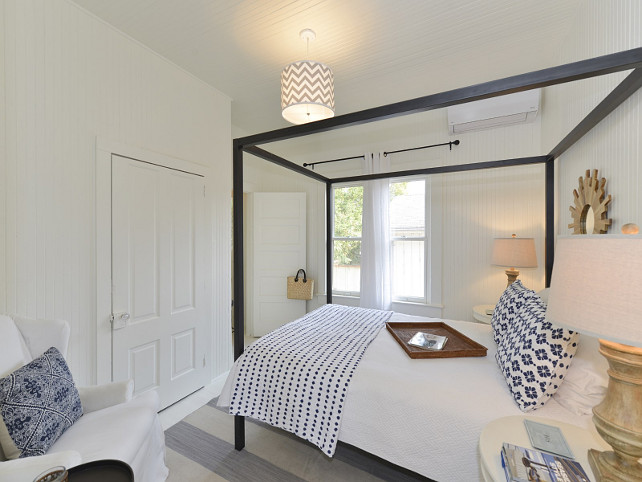 Coastal Bedroom with white beadboard walls and blue and white decor.