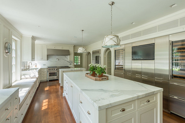 Kitchen. #Kitchen #Marble kitchen features Grosvenor 1-Light Pendants illuminating white marble top island fitted with plenty of storage across from long built-in window seats with storage drawers below. Shaker kitchen cabinets are paired with white marble countertops and white marble slab backsplash framing stainless steel range hood over swing-arm pot filler and high-end stainless steel stove placed in front of a secondary kitchen island. Arched doorways flank built-in, glass-front refrigerator beside wall of stainless steel cabinets fitted with flatscreen TV niche as well as glass-door wine coolers on either side.