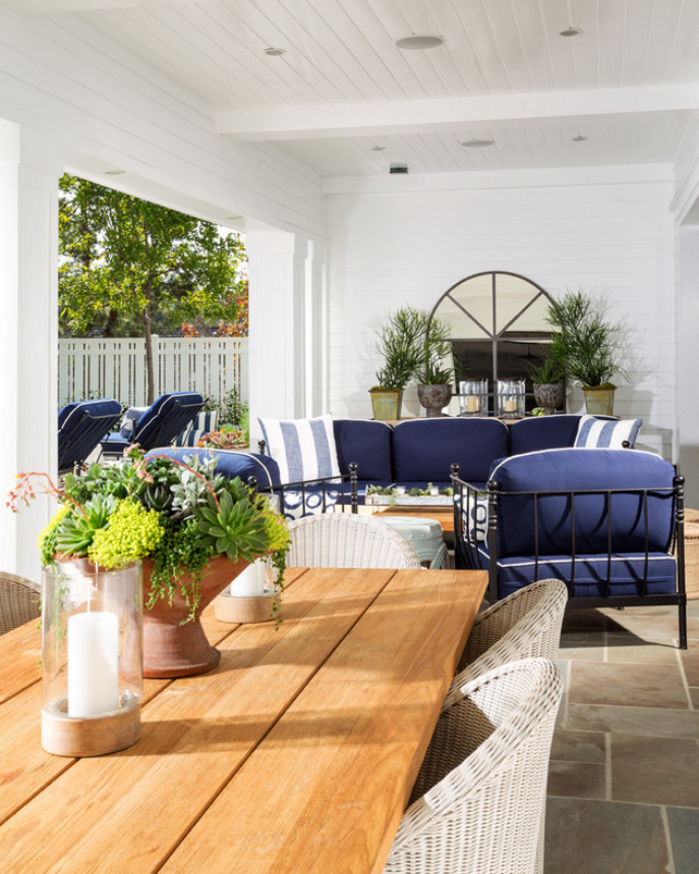 Covered patio. Covered patio layout. This loggia features beadboard ceiling and tongue and groove wall paneling framing a palladian mirror over rustic console table placed behind an outdoor blue sofa accented with denim blue striped pillows facing a reclaimed wood coffee table flanked by jute stools atop gray slate tiled floor. Legacy Custom Homes, Inc.