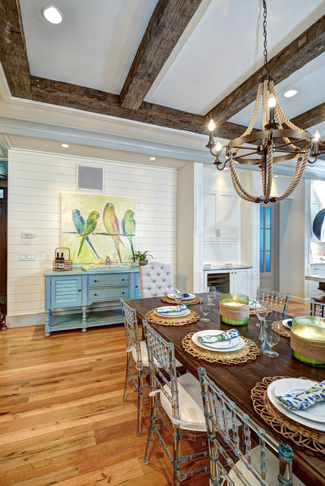Dining Room Design. Dining room Artwork. Dining room beamed ceiling. Dining room blue buffet. Dining room blue sideboard. Rectangular dining table. Rope chandelier. Rustic wood beams. Tufted chair