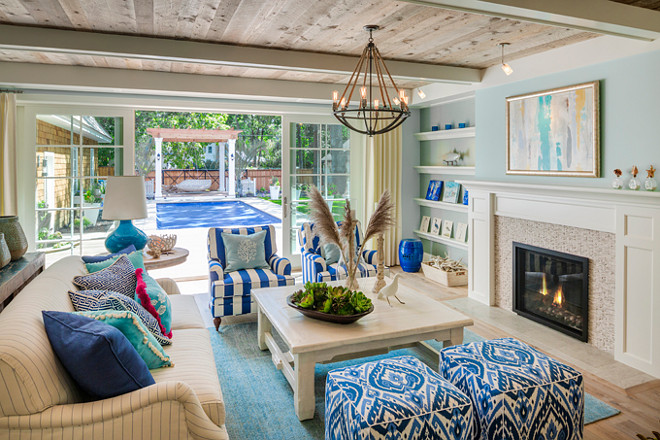 Family Room. Family room with reclaimed wood ceiling, blue walls, fireplace with shelves on the sideas, blue and white fabric and coastal decor. #FamilyRoom Great Neighborhood Homes.