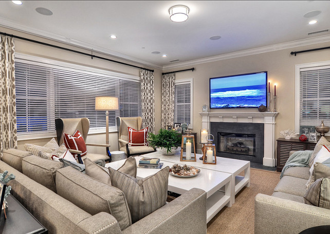 Family Room. Touches of nautical red and sea blue add color to this neutral family room. Tan couches with nail head trim surround two large white coffee tables. #FamilyRoom