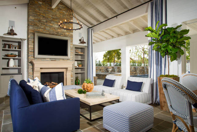 Family room. Coastal blue and white family room. The living room opens to an outdoor living area that features a TV on stone fireplace flanked by gray built-in bookcases illuminated by oil-rubbed bronze vintage lanterns across from blue sofa facing white and gray striped slipper chairs accented with navy blue pillows across from industrial coffee table atop slate tiled floor. Interiors Legacy Custom Homes, Inc.