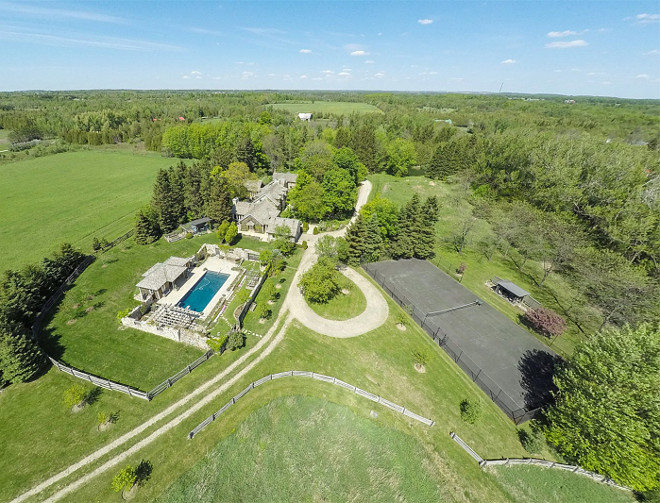 Farmhouse Arial View. French Country Farmhouse Arial View. Home Arial View. A tennis court, in-ground pool with stately pool house, and a private pond are the finishing touches on this beautiful estate. #Farmhouse #FrenchCountry #Home #ArialView