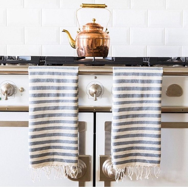 French Kitchen Ideas. French kitchen features a white French stove draped with white and gray striped Turkish towels under a subway tiled backsplash. #FrenchKitchen