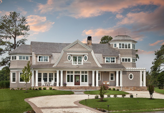 Gambrel Shingle Home Exterior. Gambrel shingle home with oval windows and front porch entry. Anthony Wilder DesignBuild, Inc.